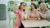clinking : Cute girls are taking selfie with smartphone sitting at table in cozy cafe and posing with coffee. Friendship, enjoyable leisure time and technology concept. Stock Footage