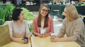 drby : Group of happy young ladies is chatting and laughing sitting at table in shopping mall cafe with to-go drinks and socializing. Youth lifestyle and fun concept.