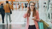 wi fi : Beautiful lady in headphones is listening to music and using smartphone walking in shopping mall with paper bags. Modern gadgets, millennials and happiness concept.
