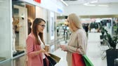 luxuoso : Happy female students are chatting and laughing standing together in shopping mall with bags and takeaway drinks. Fashionable clothing on mannequins is visible.