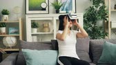 ar : Beautiful dark-haired brunette is having fun with virtual reality glasses moving head and hands wearing headset. Girl is sitting on sofa in nice modern house.
