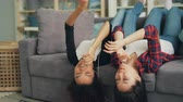 buon umore : Good-looking girls African American and Asian are enjoying favourite music through earphones and smartphone lying on couch upside-down and dancing together.