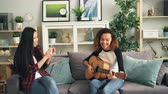 akustik : Female friends are having fun at home, African American girl is playing the guitar and Asian young woman is recording video with smartphone. Friendship and music concept.