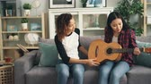 learner : Cheerful African-American girl is teaching her Asian friend to play the guitar at home. Young women are sitting on sofa holding musical instrument and talking.