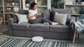 cleanness : Young African American woman is using smart phone and relaxing on couch while robotic vacuum cleaner is vacuuming apartment. Modern technologies and household concept. Stock Footage