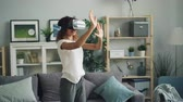 innovatief : Young African American woman is enjoying experience with augmented reality glasses wearing modern vr headset. Girl is moving hands and head standing at home.