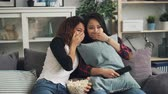 thriller : Emotional young women are watching horror film together hiding behind pillows and closing eyes. Girls are eating popcorn sitting on sofa in modern apartment.