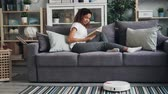 cleanness : Good-looking African American student is turning on robotic cleaner and reading book enjoying hobby and relaxing on couch while gadget is cleaning floor.