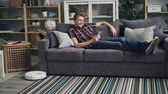 cleanness : Smiling guy is sufring the Internet with smartphone relaxing on sofa while robotic vacuum cleaner is cleaning floor removing dust from carpet. Gadgets and housekeeping concept. Stock Footage
