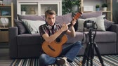 チュートリアル : Handsome guy vlogger is recording video for subscribers teaching to play the guitar holding musical instrument and talking. Man is using camera on tripod. 動画素材