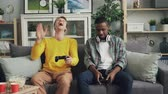 afrikai etnikai : Emotional young people African American and Caucasian are playing video game at home then talking sitting on sofa at home spending time together. Youth and fun concept.