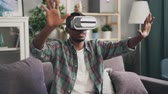 ar : African American young man is playing game in augmented reality glasses having fun alone at home wearing headset. Millennials and gadgets concept.