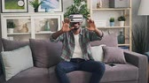 ar : African American guy is using virtual reality glasses smiling and laughing sitting on couch and moving hands enjoying new experience. Millennials and devices concept.
