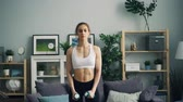 motiviert : Strong young woman in sportswear is doing sports exercises with heavy dumbbells in apartment lifting weight raising arms training muscles. Bodybuilding and youth concept.