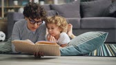 interessante : Young woman mommy is reading book to curious boy discussing story lying on floor at home and enjoying leisure time and childrens literature. House and hobby concept. Vídeos