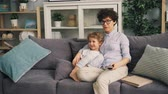 őrzés : Mother and little son are watching TV at home talking and smiling sitting on sofa together enjoying cartoons. Modern technology and childhood concept. Stock mozgókép