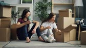 wazon : Happy couple is unpacking things after relocation opening box and looking at photos talking sitting on floor together. Moving to new house and relationship concept.