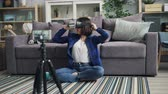 ar : Cute female vlogger is recording video about trendy vr glasses wearing modern device and talking sitting on floor at home and using smartphone camera.