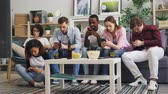 prohlížení : Multiracial group of friends girls and guys is using smartphones touching screen sitting on sofa at home focused on gadgets. Modern people and devices concept. Dostupné videozáznamy