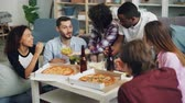 rozmowa : Young people cheerful men and women are eating crisps and popcorn and chatting relaxing during indoor party in apartment. Delicious pizza is visible on table. Wideo