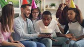 bem : Happy African American man is blowing candles on birthday cake and laughing during surprise party at home while his friends congratulating clapping hands. Youth and holidays concept. Vídeos