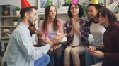 tebrik etmek : Young lady is making wish then blowing candles on birthday cake at party with friends at home while men and women singing then clapping hands. Holiday and apartment concept. Stok Video