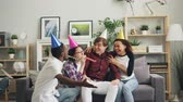 pískat : Group of friends is congratulating sad young man on birthday bringing cake singing song blowing party whistles. Holiday, friendship and apartment concept.