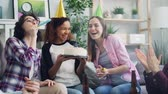 assobio : Slow motion of happy African American woman blowing candles on birthday cake celebrating with friends laughing having fun. Men and women blowing party whistles and throwing confetti. Vídeos