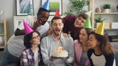 assobio : Happy guy singing with friends wearing party hats then making wish and blowing candles on birthday cake while men and women clapping hands and talking