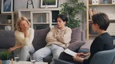 juvenil : Unhappy family mature mother and teenage son are talking to psychotherapist in modern clinic sitting on couch and fighting. Communication and psychology concept.