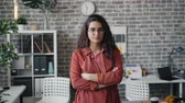 zakenvrouw : Portrait of serious young woman with long curly hair standing in office room alone with arms crossed and looking at camera with straight face. Business and people concept.