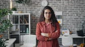 kamer : Portrait of pretty female entrepreneur standing in office with crossed arms looking at camera with strict face. Beautiful people, businesswoman and workspace concept.