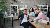 gerät : Joyful young people male and female coworkers are taking selfie with smartphone camera in office posing with funny faces and hand gestures. Youth and job concept. Stock Footage