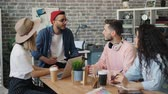 opinie : Creative team of designers men and women are speaking in office sitting around table brainstorming at work. Millennials, conversation and workplace concept. Stockvideo