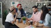 lachen : Group of men and women is having conversation laughing and talking during business meeting in creative office. Casual discussion, millennials and work concept.