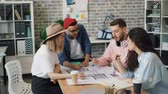 opinie : Group of creative architects young men and women is talking pointing at building plan sitting around table in modern office. Professionals and workplace concept. Stockvideo