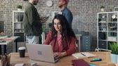 motion timelapse : Zoom in time-lapse of attractive young woman hipster using laptop working at project in office while men and women are rushing around. Business and creativity concept. Stock Footage
