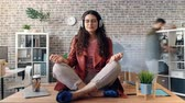 motion timelapse : Time-lapse of female employee listening to music in headphones enjoying work break sitting in lotus pose on desk relaxing. Happy youth and relaxation concept.
