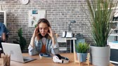 stillness : Time-lapse of depressed girl tired employee sufffering from headache in office touching head sitting at desk while coworkers are moving around doing job. Stock Footage