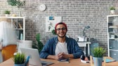 motion timelapse : Zoom out time-lapse of happy successful young man smiling looking at camera in office room siting at desk when employees are moving around. Business and youth concept. Stock Footage