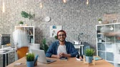 motion timelapse : Time-lapse of happy guy entrepreneur sitting at office desk smiling and looking at camera while busy employees are rushing around doing work. Business and happiness concept. Stock Footage