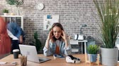 cansado : Zoom out time-lapse of tired young woman exhausted employee touching head in office feeling sick sitting at desk while busy coworkers are rushing around.