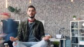 motion timelapse : Time-lapse of bearded young man resting at work sitting in lotus pose on desk relaxing releasing stress. Creative workspace, healthy youth and business concept. Stock Footage