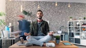 motion timelapse : Time-lapse of handsome young man hipster relaxing in lotus position on desk in office while colleagues are moving around. Stress management and job concept.