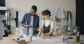 werkstatt : Dressmakers African American guy and Caucasian woman are using tablet at work and measuring fabric pieces designing clothes together. Technology and work concept. Stock Footage