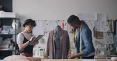 ölçüm : People designers African American guy and Caucasian lady are measuring clothing on tailors dummy and using tablet to put in measurements. Technology and fashion concept. Stok Video