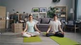 accogliente : Girl and guy attractive young people meditating in lotus position in apartment enjoying relaxation and spiritual experience. Home and yoga practice concept.