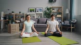 stillness : Young man and lady beautiful couple are relaxing in lotus position meditating on floor at home with hands on knees. Meditation and modern lifestyle concept.