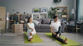 kroutit : Cute couple girl and guy are practising yoga in apartment sitting on floor twisting body enjoying physical exercise and active lifestyle. Modern youth and sports concept. Dostupné videozáznamy