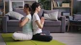 stillness : Side view of young couple man and woman meditating sitting back to back on floor with hands in namaste. Relaxation, meditation and healthy youth concept. Stock Footage